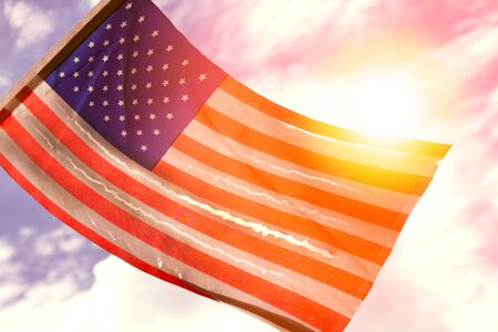 Old American flag dilapidated perforated burned grunge tattered by golden sunset light 스톡 콘텐츠
