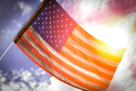Old American flag dilapidated perforated burned grunge tattered by golden sunset light Stock Photo