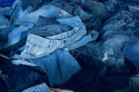 Stack of various shades blue jeans. Pile Blue denim jeans texture banner. Canvas denim fashion texture