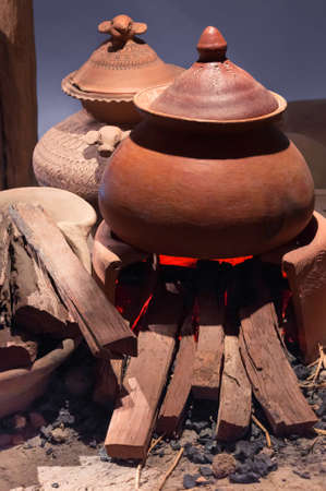 Traditional pottery clay pot on brick campfire with fire