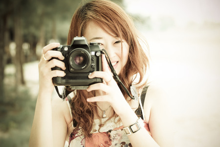 A beautiful female photographer with her digital camera photo