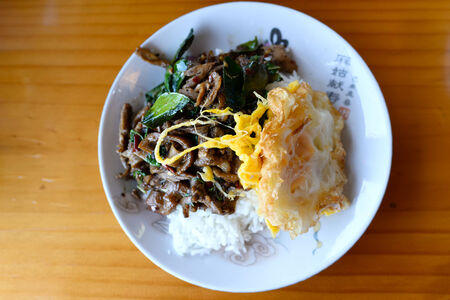 Rice topped with stir-fried basil duck and fried egg. photo
