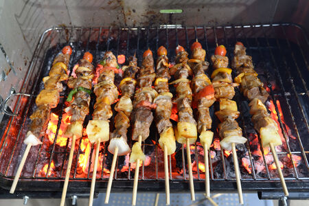 sizzling: kebabs skewered with peppers and tomato sizzling over the coals of a barbecue