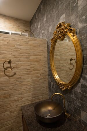 to mirror: Gold mirror in bathroom.