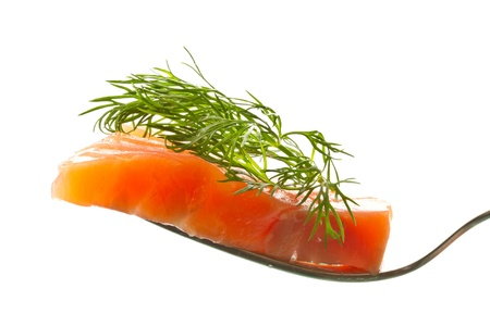 a piece of salted trout on a fork over white background photo