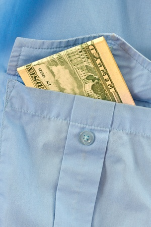 the money is in the pocket of a blue shirt Stock Photo