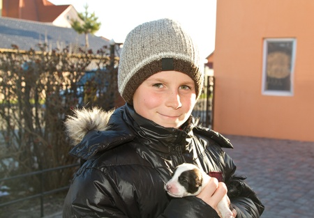 adolescent boy is holding a small puppy photo