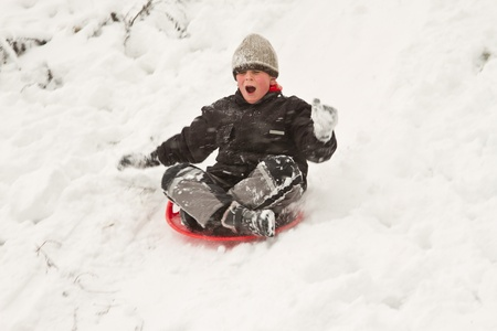 a boy goes down on sledges from a hill in winter photo