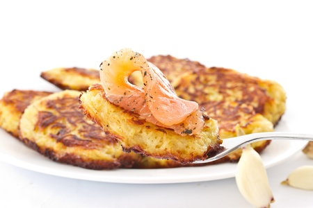 fried potato pancakes with salted salmon on a white background photo