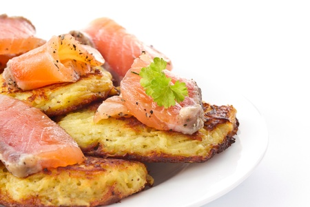 fried potato pancakes with salted salmon on a white background photo