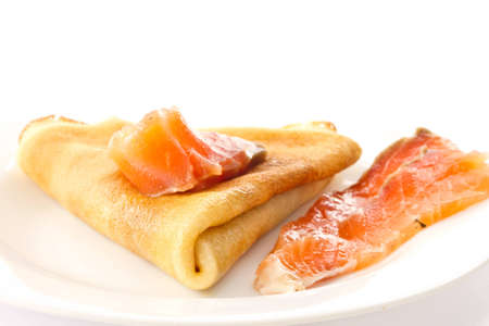 Pancakes with salted red fish on a white plate photo