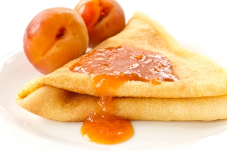sweet pancakes with apricot jam on a white plate photo