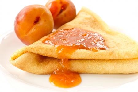 zoete pannenkoeken met abrikozenjam op een witte plaat