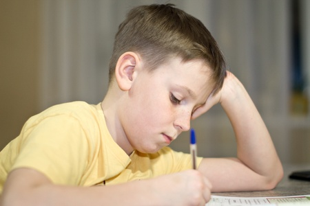 children writing: a boy student learns lessons while sitting at a desk