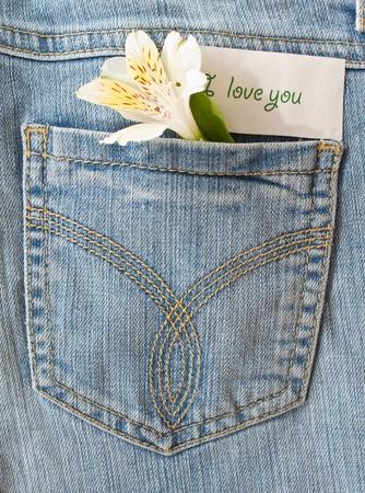 declaracion de amor: flor y una declaraci�n de amor en el bolsillo trasero de los pantalones vaqueros Foto de archivo