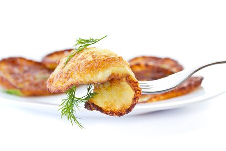 fried potato pancakes with dill on white background photo
