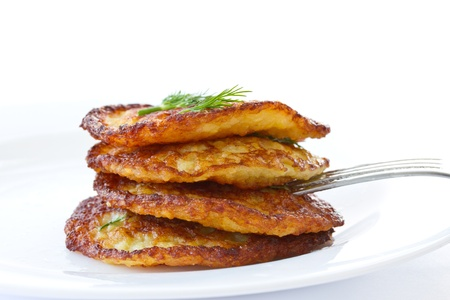 fried potato pancakes with dill on white background