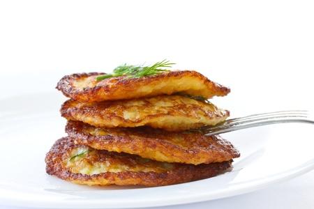 gebakken aardappel pannenkoeken met dille op een witte achtergrond