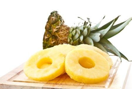 peeled slices of pineapple on a white background