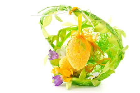 Crocuses and light green egg in a basket on a white background photo