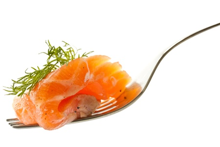 salted salmon on a fork close up on a white background photo
