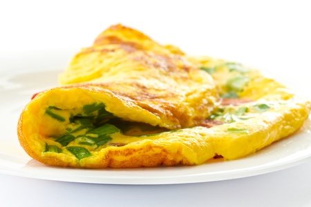 an omelette: scrambled eggs with fresh herbs on a white background