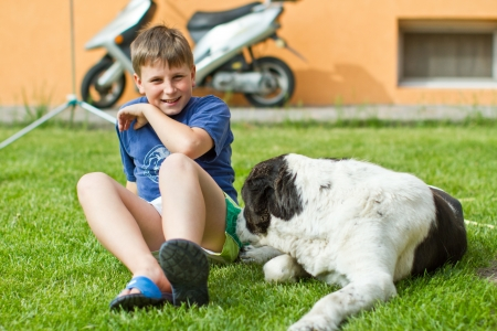 the boy with his dog sitting on grass photo