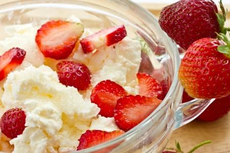 leche y derivados: Dulce de leche queso cottage con fresas en un plato Foto de archivo