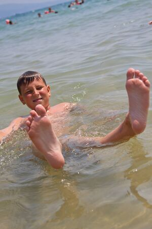 happy tanned boy in the summer sea photo