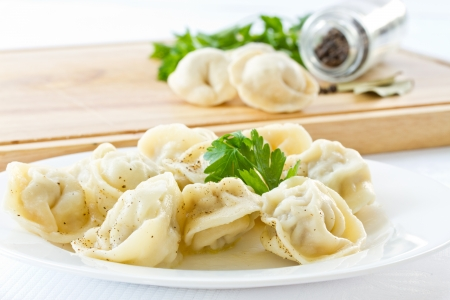 Boiled pelmeni in a bowl with spices on a light background Stockfoto
