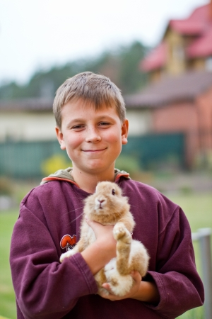 happy boy with homemade decorative rabbit outdoors photo