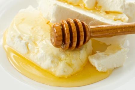 cottage cheese: latte ricotta con miele sul piatto bianco