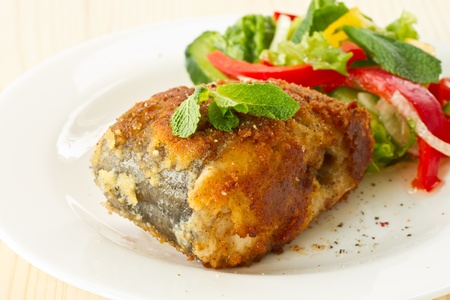fish fried in breadcrumbs on a plate with vegetables photo