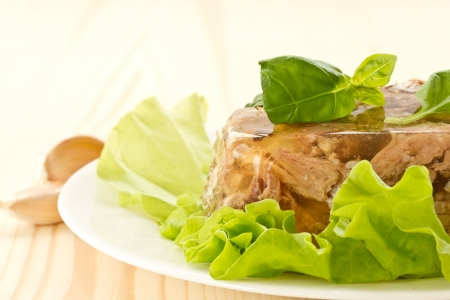 meat jellied in jelly on lettuce leaves with a basil photo