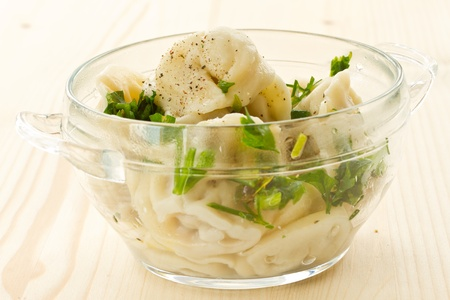 Boiled pelmeni with butter and herbs in a bowl photo