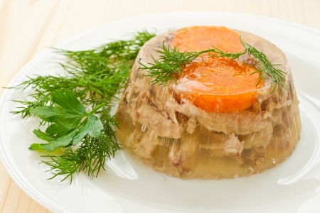 jellied meat and vegetables on a white plate
