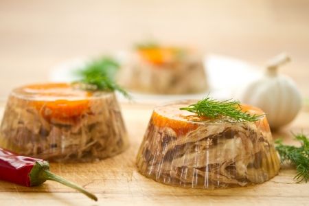 jellied meat and vegetables on a wooden background