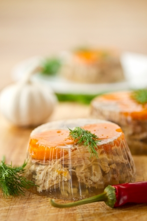 jellied meat and vegetables on a wooden background photo