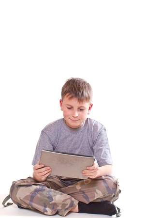 only boys: Teen plays on the tablet computer on a white background