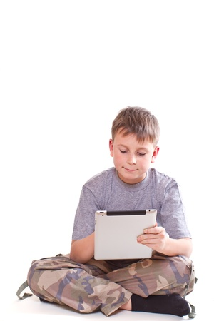 Teen plays on the tablet computer on a white background Stock Photo - 16752572