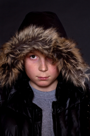 portrait of a boy in a winter jacket on a black background photo