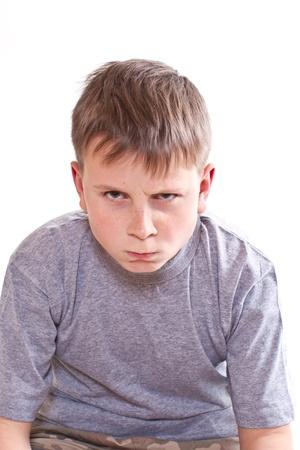 expresiones faciales: retrato de un muchacho adolescente enojado sobre fondo blanco