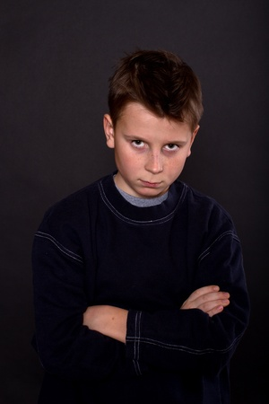 10 to 12 years: portrait of teenage boy on a black background