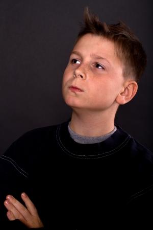 10 12 years: portrait of teenage boy on a black background
