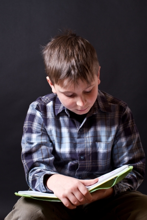 boy with a book on a black background Stock Photo - 16887898