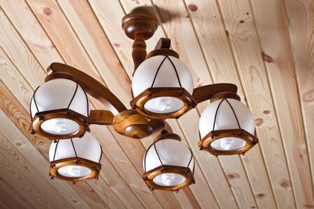 beautiful wooden electric chandelier on wooden ceiling photo