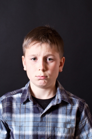 Portrait of the offended boy on a black background Stock Photo - 16887905
