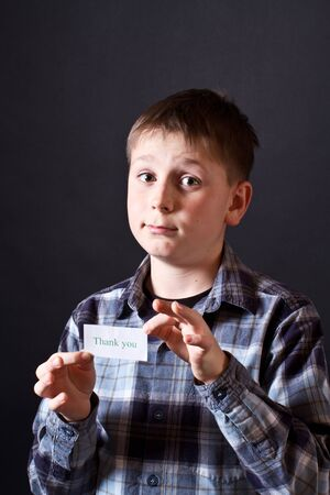 boy shows a card with gratitude on a black background photo