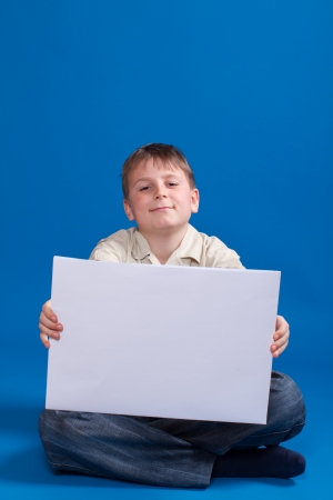 boy holding a blank form on a blue background photo