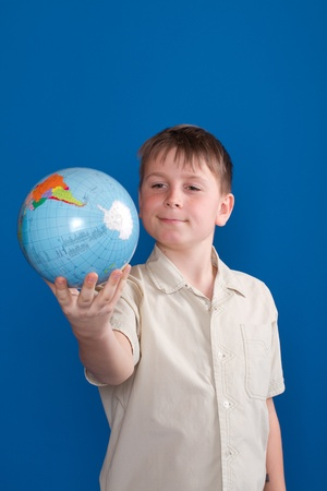 boy holding a globe on a blue background photo